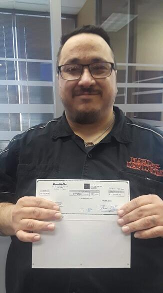 Brian Barbosa holds Rumble On's sweepstakes check